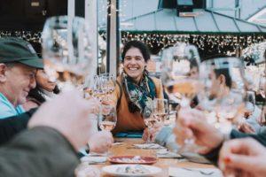 grupo de viajantes brindando com taças de vinho durante um passeio a pé pela gastronomia e cultura