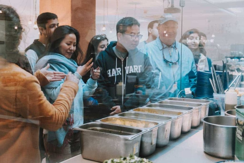 a group of travelers looking a dish being made while enjoying a food and culture walking tour