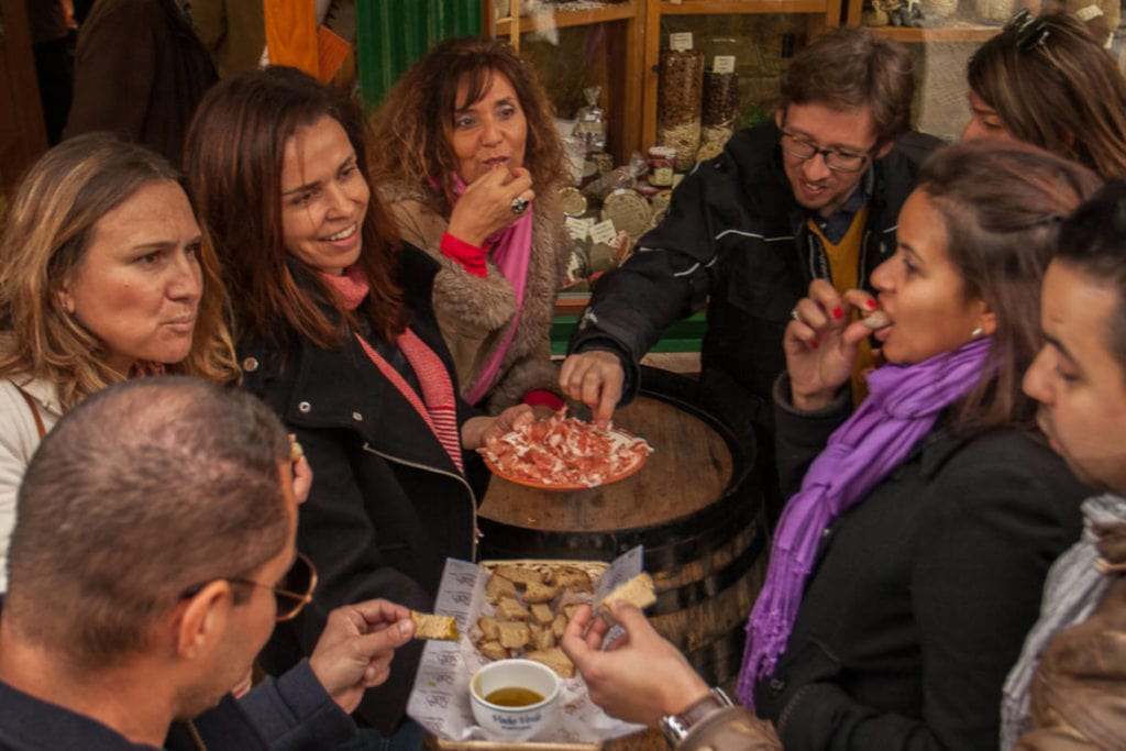 A group of travelers tasting local food during a food tour in Lisbon