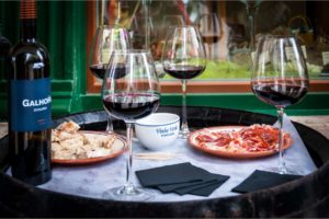 a tray with wine glasses, a bottle of wine and Portuguese appetizers on two dishes