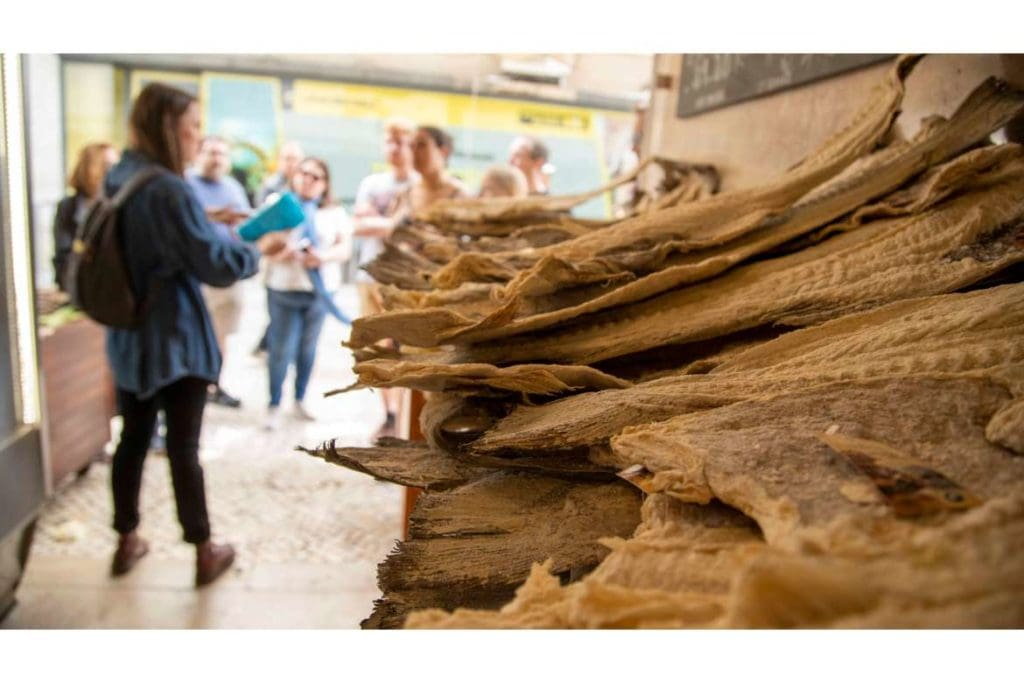 at the front a pile of bacalhau, Portuguese salted cod fish on the counter, behind a food tour guide with a group of food travelers during a walking tour in Lisbon