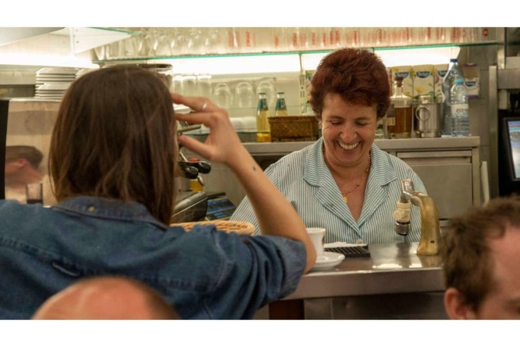 a Portuguese waitress smiling behind the counter while serving local food to a tourist during a food tour