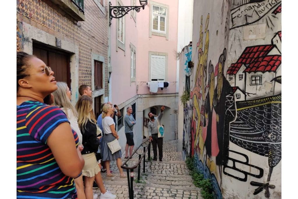 a food tour guide showing paiting on the wall in a small street aisle during a food walking tour in Lisbon