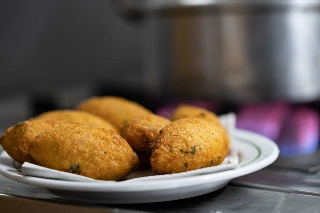 a plate with Bolinhos de Bacalhau (Cod Fritters) ordered during a food tour in Lisbon