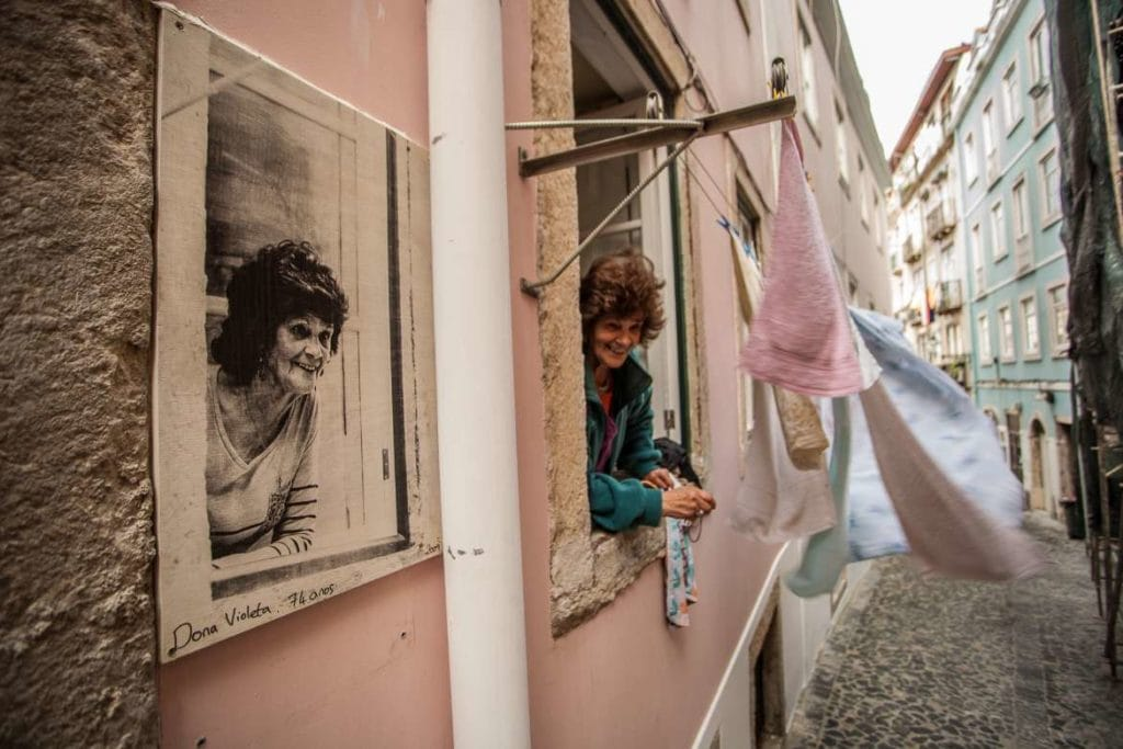 a local woman in Lisbon on the window with a paiting of herself on the same position on the side
