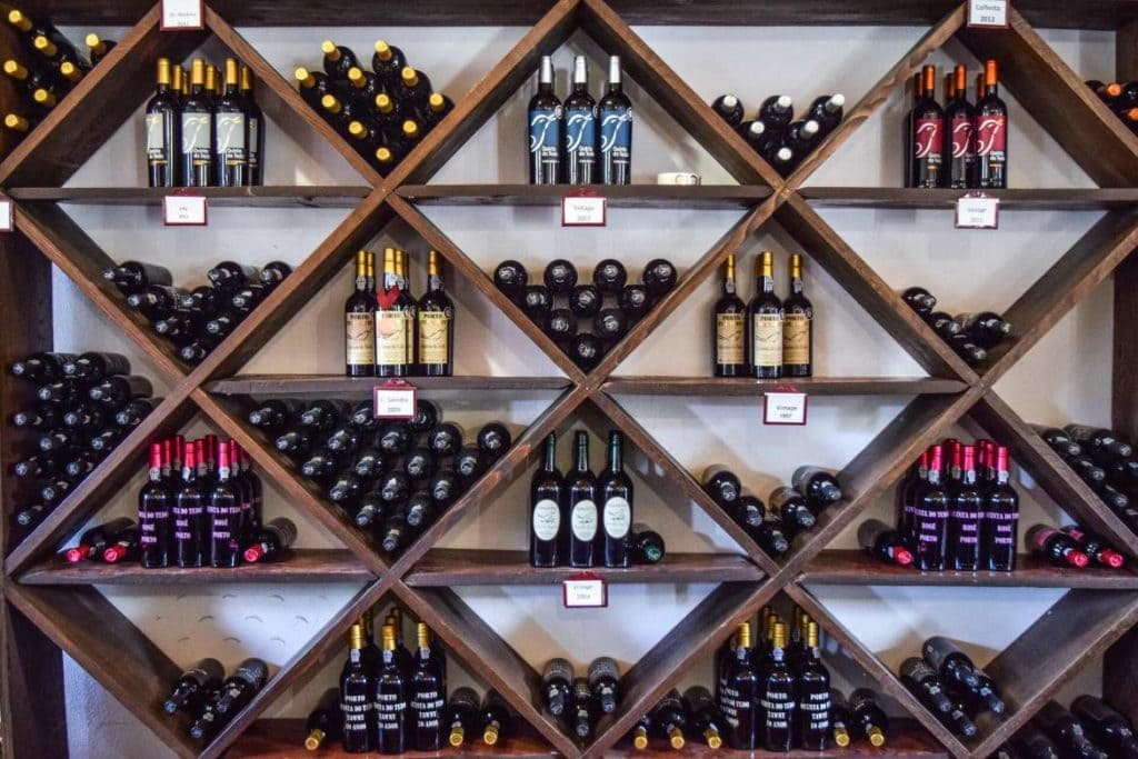 wooden shelves with wine bottles inside a wine store in the Douro