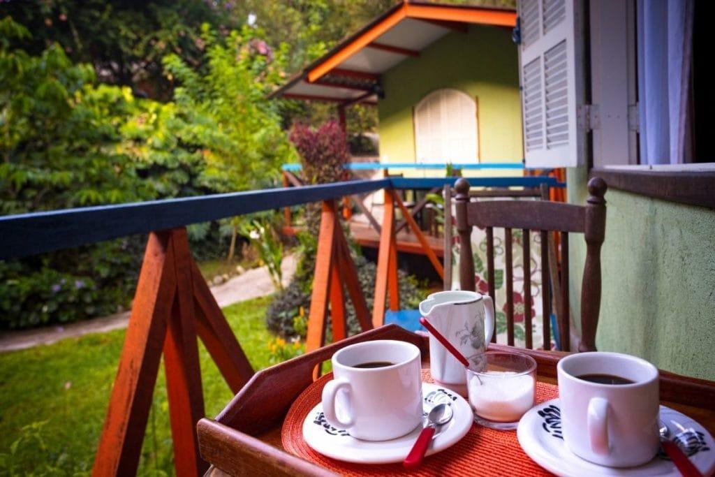 duas xícaras de café e uma tigela de açúcar em uma bandeja na varanda de um hotel rural em Minas Gerais