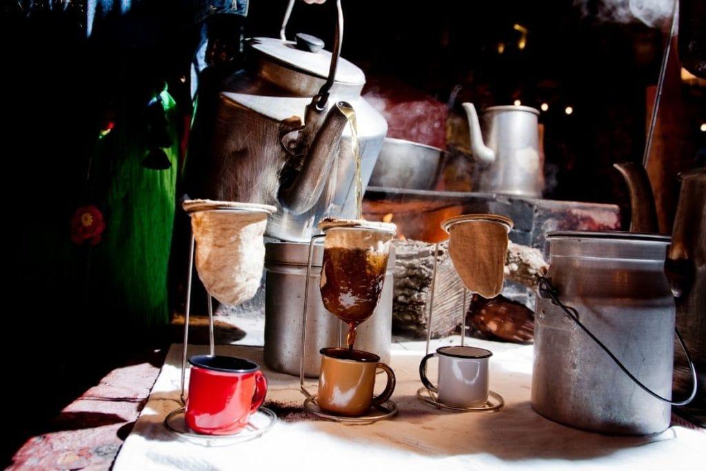 uma panela com água fervida sendo despejada sobre 3 xícaras de café com um filtro de pano, a maneira típica de fazer café brasileiro