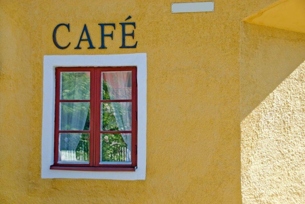 uma parede amarela com uma janela e uma placa escrita Café