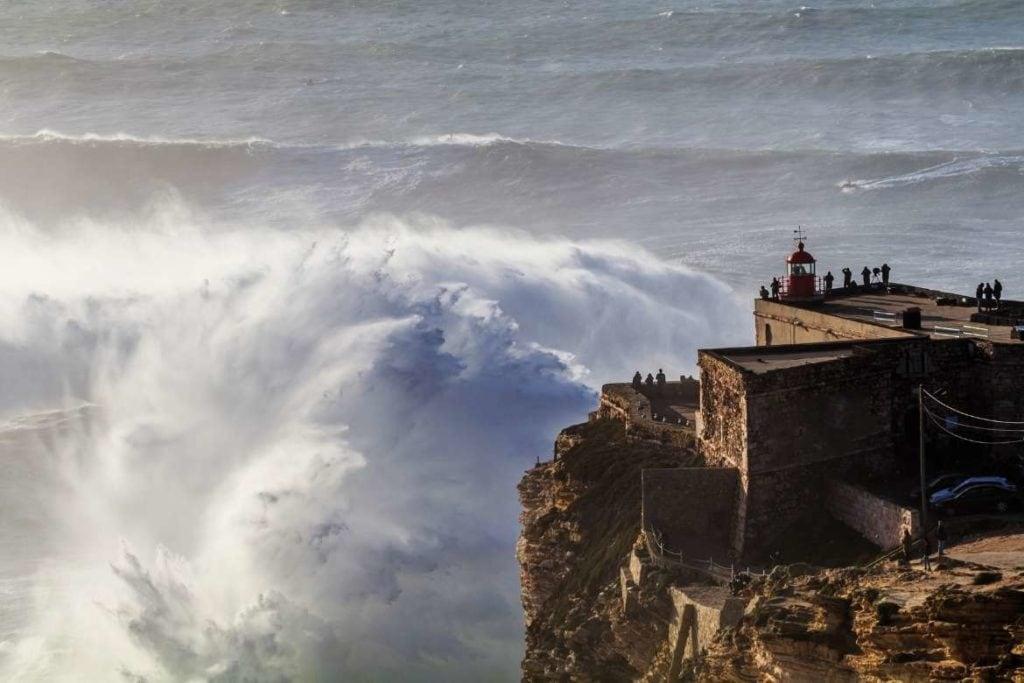 Onda gigante quebrando ao lado de um mirante na Nazaré, um destino de praia no centro de Portugal