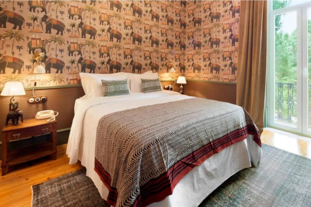 Photo of Casa Oliver Boutique B&B bedroom with a double bed and decorated with Elephant-stamp themed wallpaper