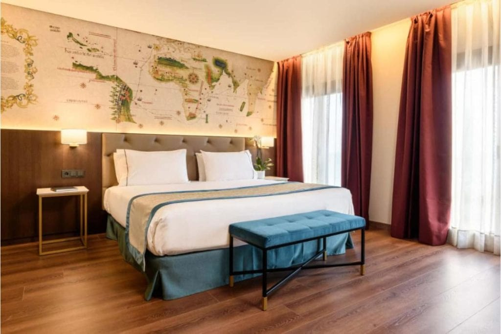 Photo of Eurostars Museums bedroom with double bed, the wall is decorated with a vintage world map
