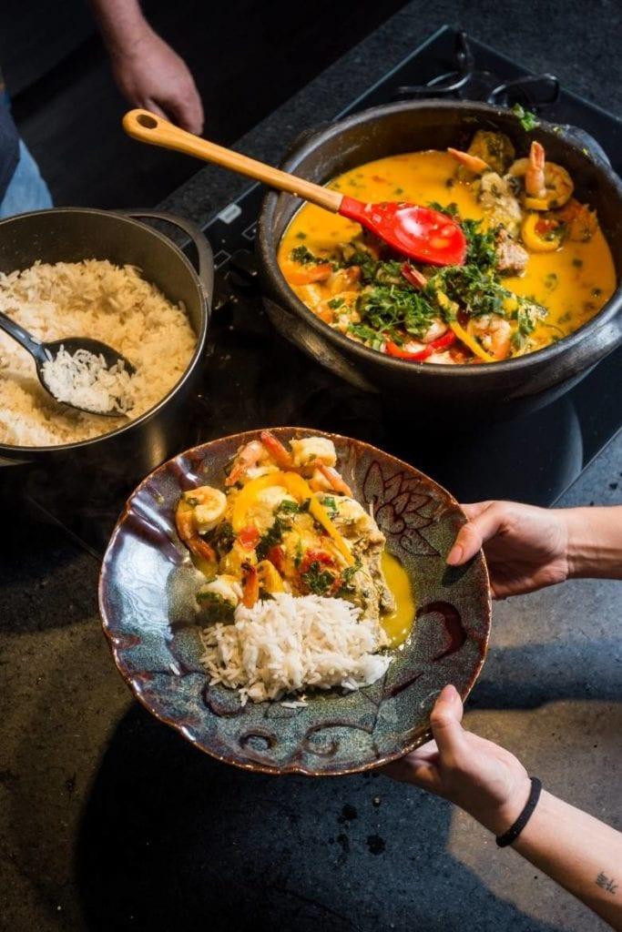 mãos de uma mulher segurando um prato com moqueca e arroz. ao lado de uma moqueca em uma panela de barro e uma panela de arroz