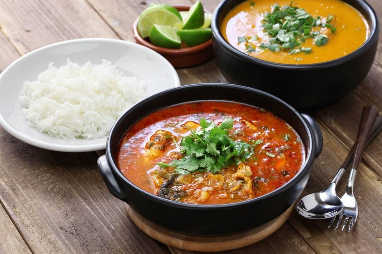 moqueca capixaba servida em panela de barro acompanhadas com uma tigela de pirão e outra de arroz branco