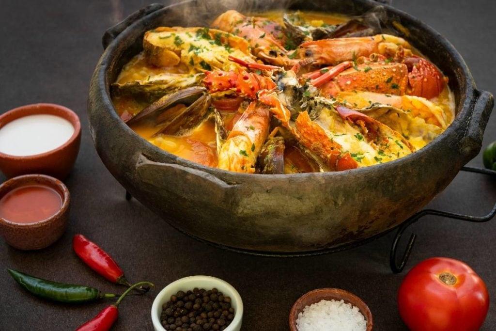 panela de barro com moqueca de frutos do mar no centro com ingredientes da moqueca em tigelas pequenas ao redor