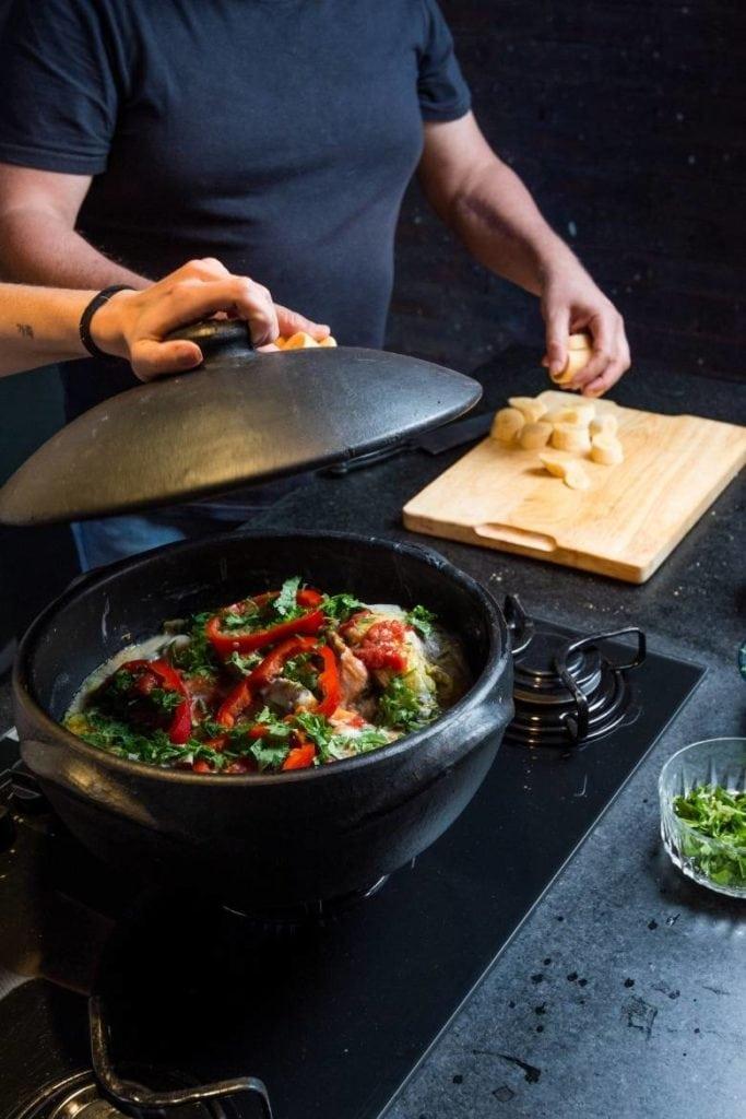 uma mão segurando a tampa, prestes a cobrir a panela de barro com ingredientes em camadas para cozinhar a moqueca brasileira