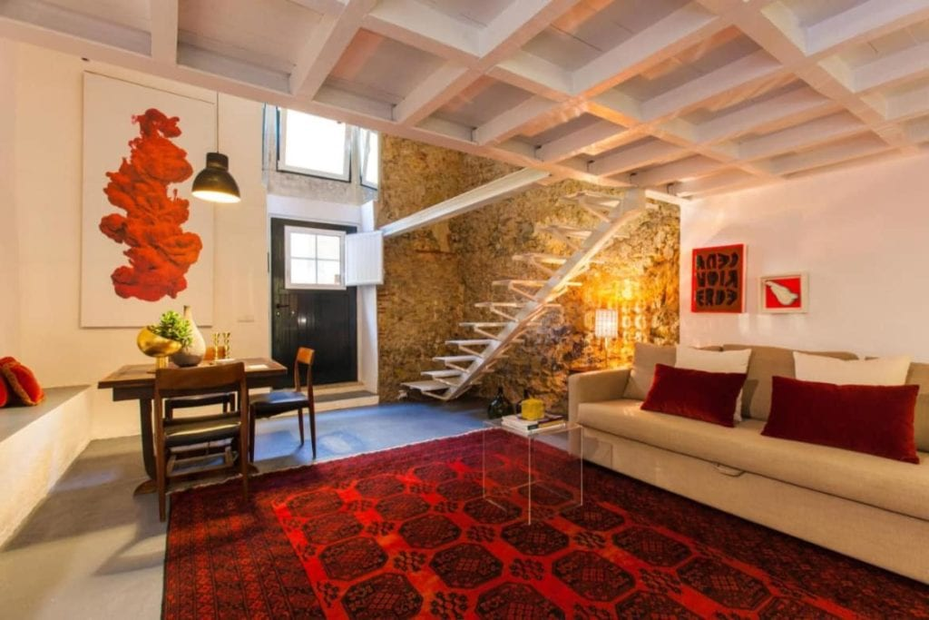 Photo of Lisbon Unique Apartments living room in the ground floor - with sofa, a table and the stair to the second flor on the right