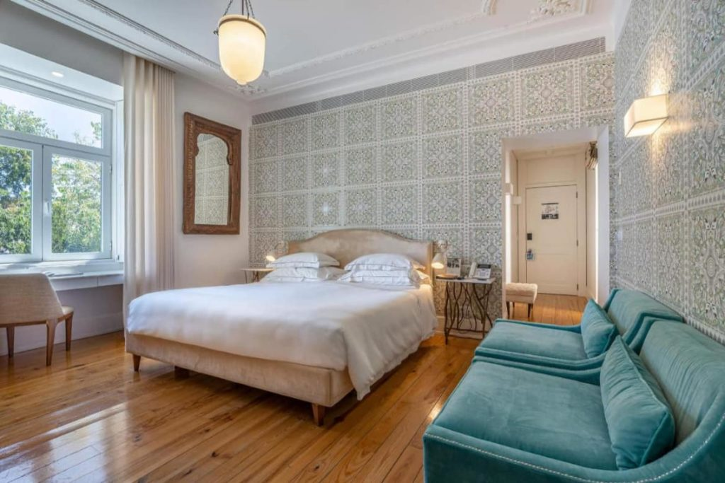 Photo of Santiago de Alfama bedroom with a double bed in the center, window on the left side and a blue velvet sofa at the right side