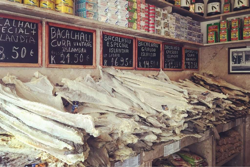 a store in Portugal with plenty of bacalhau cuts layered on top of each other on the counter
