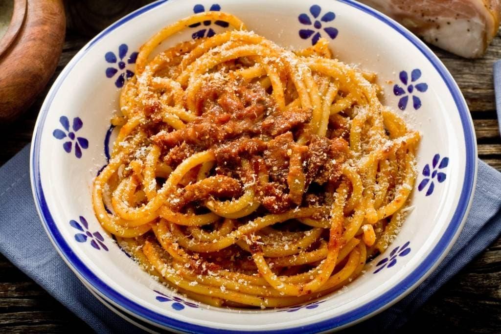 Roman pasta alla amatriciana served on a white plate with minimalist blue pattern