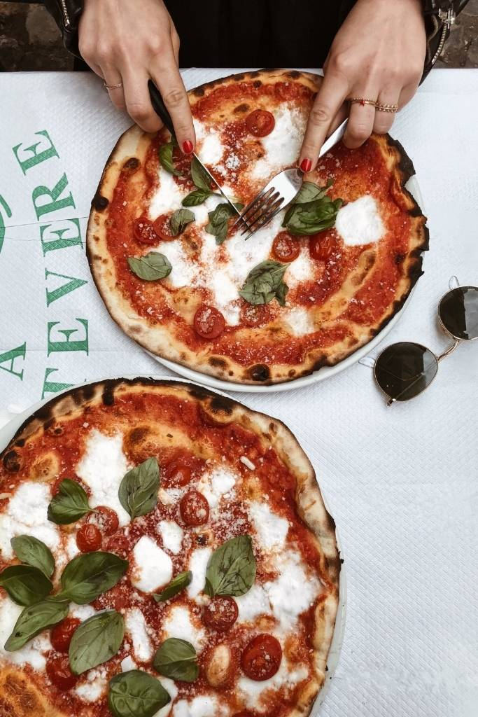 two pizzas on a plate with female hands cutting the pizza with fork and knife